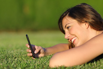 Profile of a funny girl using a smart phone on the grass