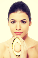 Beautiful woman's face with avocado.