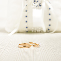 Pair of wedding rings in front of luxury cushion