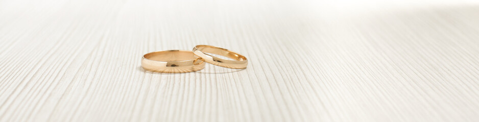 Two gold wedding rings on the bright background