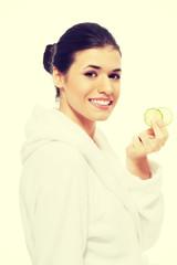 Beautiful woman in bathrobe holding cucumbers.