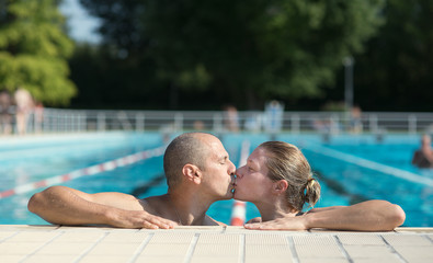 Couple kissing by a pool