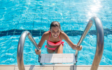 One girl climbing the steps of a swimming pool