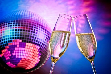 champagne flutes on sparkling blue and violet disco ball