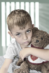 Small lonely boy with a teddy bear