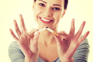 Young beautiful woman holding broken cigarette.