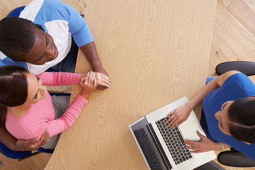 Overhead View Of Couple Talking To Financial Advisor
