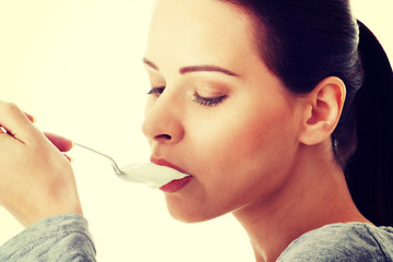 Young casual woman eating a yoghurt.