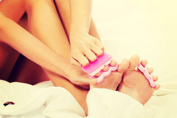Attractive woman painting her toes in bed.