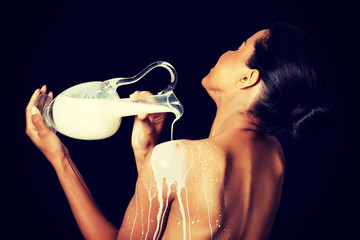 Beautiful naked woman is pouring milk on her back.