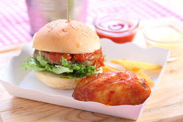 homemade hamburgers and chicken wing on wooden board