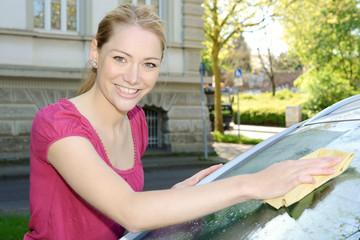Frau wischt Windschutzscheibe mit Fensterleder