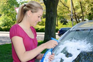 Frau mit Scheibenreiniger-Spray an Auto