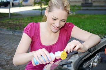 Frau füllt Wasser und Reiniger in Waschanlage