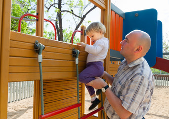 girl with dad on  playground.