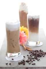 Three Ice coffee with flower and coffee beans on a table