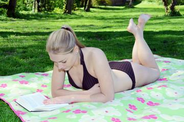 Twen im Bikini liest Buch auf Picknick-Decke
