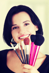 Young make-up artist woman holding brushes