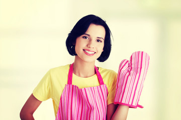 Young housewife in pink apron ang glove