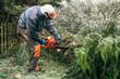 Professional gardener using chainsaw