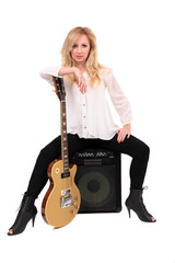 Woman with guitar sitting on an amplifier