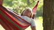 Young woman relaxin on a hammock in nature