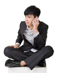 Asian business man take a call and sit on ground.