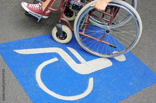 Leinwanddruck Bild Frau mit Rollstuhl auf Behinderten-Parkplatz