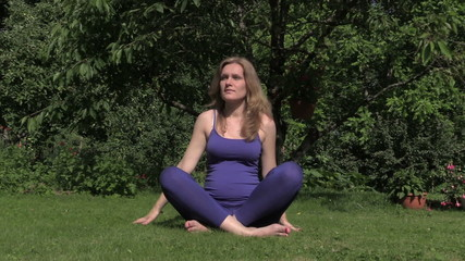 Healthy pregnant woman do yoga exercise sit on grass in garden