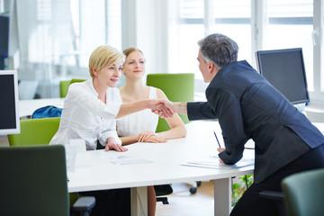Geschäftsleute am Tisch schütteln die Hände