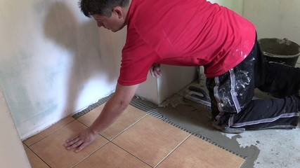 Tiler man lay floor tiles. Right side sliding