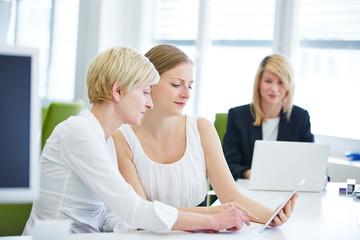 Geschäftsfrauen arbeiten mit Tablet Computer