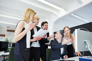 Team im Büro schaut auf defekten Computer