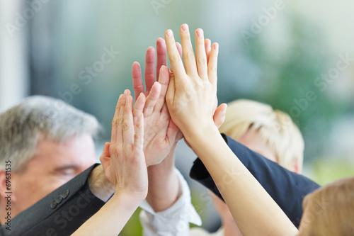 Leinwandbild Motiv Hände geben sich High Five im Büro