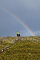 Bicycle tourist and rainbow