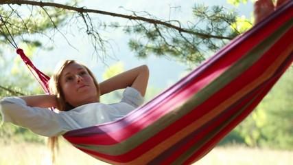Woman relaxing in a hammock slow motion