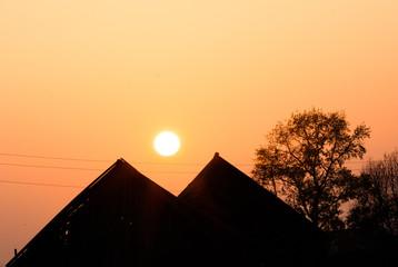 Солнце садится между крышами двух домов