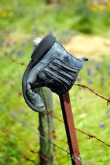 Bota vieja en la valla de alambre