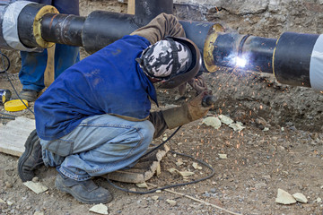 welder welding underground steel pipe kneels on ground