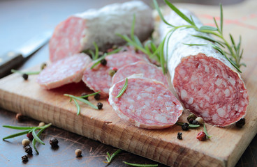 Salami sausage on a wooden cutting board with herbs