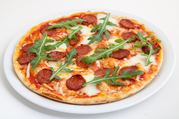 pizza with salami, cheese and arugula on white plate