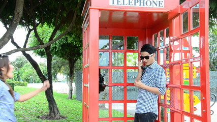 Men were talking telephone in a public phone. HD