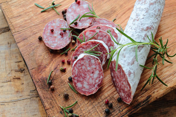 Salami sausage with herbs on a wooden board