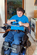 Spastic young man confined to a wheelchair, dialing a phone numb - 69639141