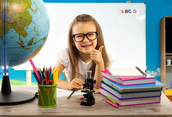 Girl showing thumb up sitting with globe at desk