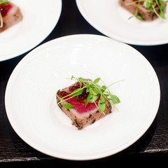 juicy filet mignon cutted on white plate with rocket