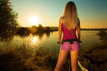 Pretty woman on bicycle relaxing at Sunset