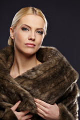 Woman in luxury fur coat. Vintage style. Brown background.