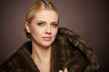 Portrait of beautiful young woman wearing fashionable fur , look