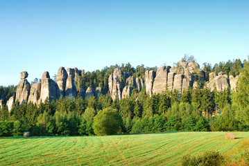High sandstone towers rising from a forest in Adrspach
